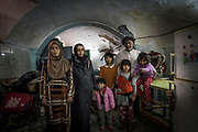 Nuhad Hamdoon (left), her daughter Sawsan, and her daughter's husband Taha Younis stand with their children in the basement of the family's home in the old city of Mosul. <br />