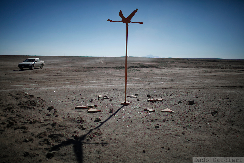 A compass rose with a metal in the form of a flying Chilean Flamingo (Phoenicopterus chilensis) sits at the entrance of the Uyuni salt desert in Bolivia, Thursday, July 29, 2010.   A late nidification triggered by extreme cold weather and severe droughts in their habitats, could be the cause why dozens of these graceful baby birds started to appear in cities that surround the salt flats of Uyuni. Unable to fly and being migratory animals they may have been left behind by their relatives on their routes escaping from the winter in the salty lagoons they live and reproduce. Hungry, disoriented and often too weak to fly or fend for themselves and find food on a new and hostile environment they are dying frozen, being smashed by touristic ATVs or trucks carrying mined salt across the flats or just being carried away by people that feel sorry and try to protect them from the cold in their houses.   (Photo Dado Galdieri)