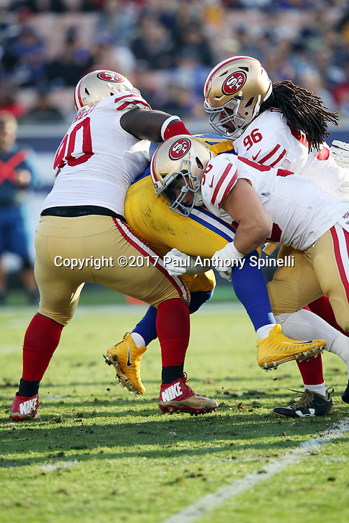 San Francisco 49ers middle linebacker Brock Coyle (50), and San Francisco 49ers defensive tackle Earl Mitchell (90), and San Francisco 49ers defensive tackle Sheldon Day (96) lift and gang tackle Los Angeles Rams running back Malcolm Brown (34) during the 2017 NFL week 17 regular season football game against the Los Angeles Rams, Sunday, Dec. 31, 2017 in Los Angeles. The 49ers won the game 34-13. (©Paul Anthony Spinelli)
