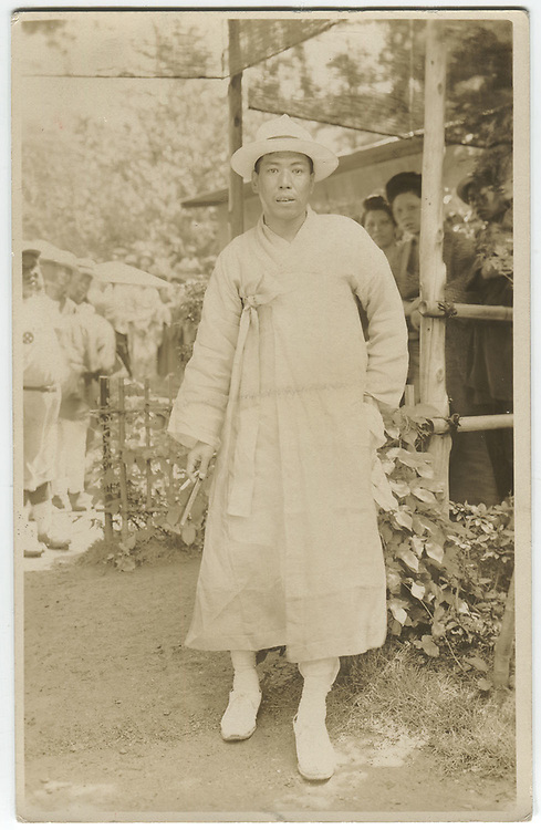 Actor in Korean Hanbok kimono, baseball team in background, Japan, 1920s, silver gelatin bromide post card.<br />