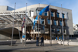 Edinburgh, Scotland, UK. 15 March, 2019. Men lowering flags to half-mast at Scottish Parliament in Edinburgh in respect for those killed in terrorist attack on mosques in Christchurch, New Zealand. Scotland, UK