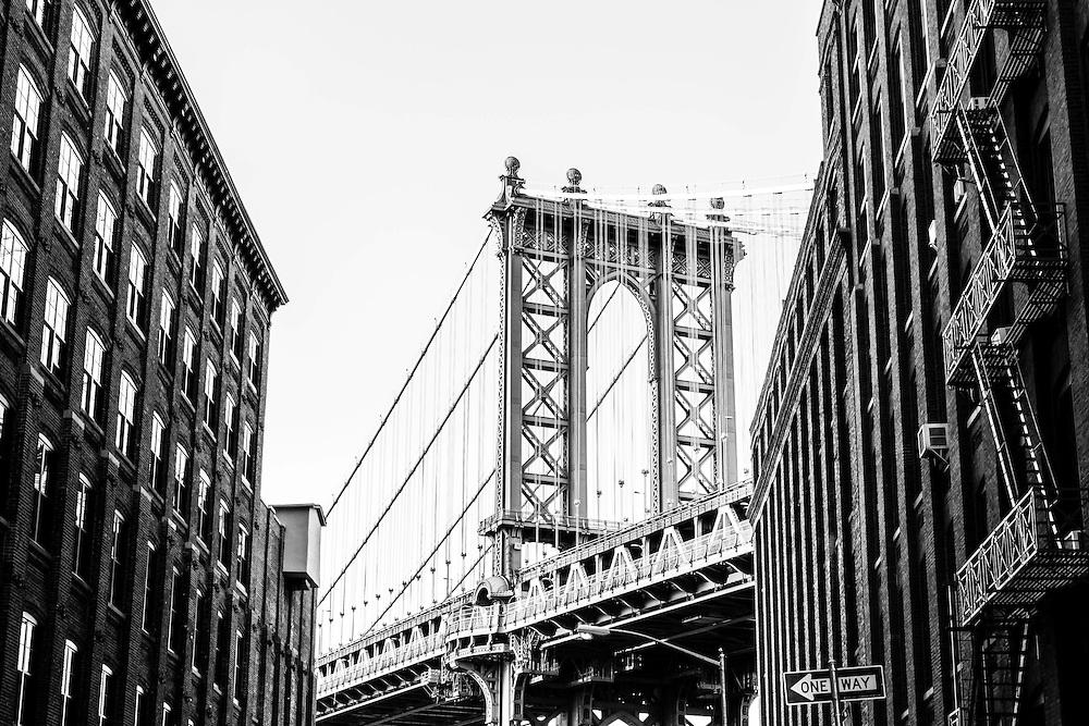 The Manhattan Bridge seen towering between the buildings on Front Street in Brooklyn, New York.