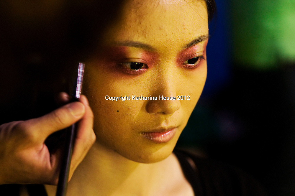 BEIJING, MAY -7, 2012 :  a model has her make-up done backstage. .Guo Pei , 45, is China's answer to haute couture. When she started out 15 years ago, there was no fashion in China .  Since then though  about everything in China has changed. Many more people are able to afford luxury products, and Chinese women, at least those who can afford it, follow international fashion trends. What makes Guo Pei different is what she puts on a runway. She employs 300 people in a workroom two hours from Beijing. She had to train them, but it?s also true that her creative freedom is tethered to relatively cheap labor. One dress alone, made entirely of golden panels, took 50,000 hours to embroider.