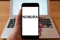 Using iPhone smartphone to display logo of Nomura Japanese financial holding company