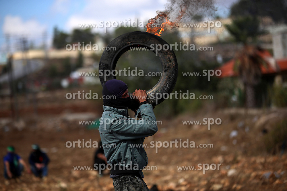 08.10.2015, Ramallah, PSE, Gewalt zwischen Pal&auml;stinensern und Israelis, im Bild Zusammenst&ouml;sse zwischen Pal&auml;stinensischen Demonstranten und Israelischen Sicherheitskr&auml;fte // A Palestinian protester carries a burning tire during clashes with Israeli security forces in Beit El, near the West Bank city of Ramallah. New violence rocked Israel and the Israeli occupied West Bank, including an incident in which men thought to be undercover Israeli police opened fire on Palestinian stone throwers they had infiltrated, wounding three of them, Palestine on 2015/10/08. EXPA Pictures &copy; 2015, PhotoCredit: EXPA/ APAimages/ Shadi Hatem<br /> <br /> *****ATTENTION - for AUT, GER, SUI, ITA, POL, CRO, SRB only*****