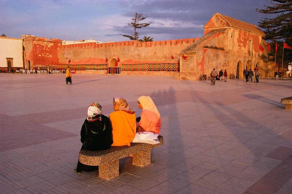 Africa, Morocco, Essaouira, three women on bench in plaza near historic stone walls