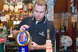 Young Polish barman pulling a pint of beer at Polish Social Club,