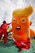 The Trump Baby sitting team dressed in red boiler suits deflate the six metre high inflatable TrumpBaby balloon for the demo on the Meadows in Edinburgh for the Scottish demonstration. United Kingdom. 14th July 2018.  (photo by Andy Aitchison / Trump Baby Sitters)