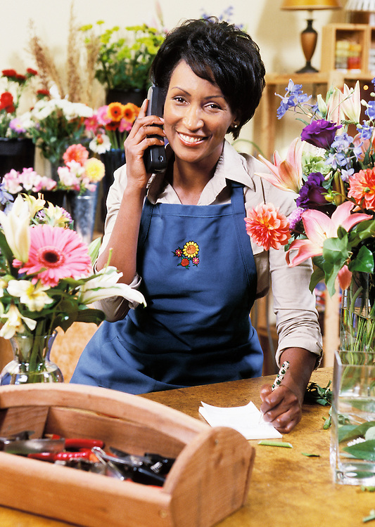 An African American woman small business owner on the phone in her shop.