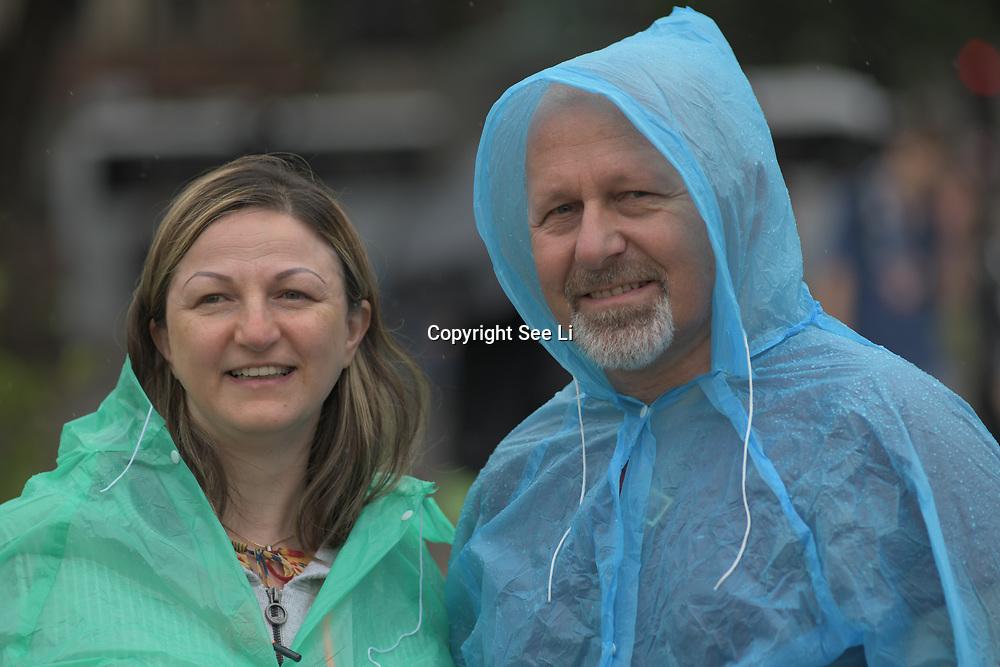 UK Weather:  A couple wearing plastic raincoat in Rainy London, UK. 19 July 2019.