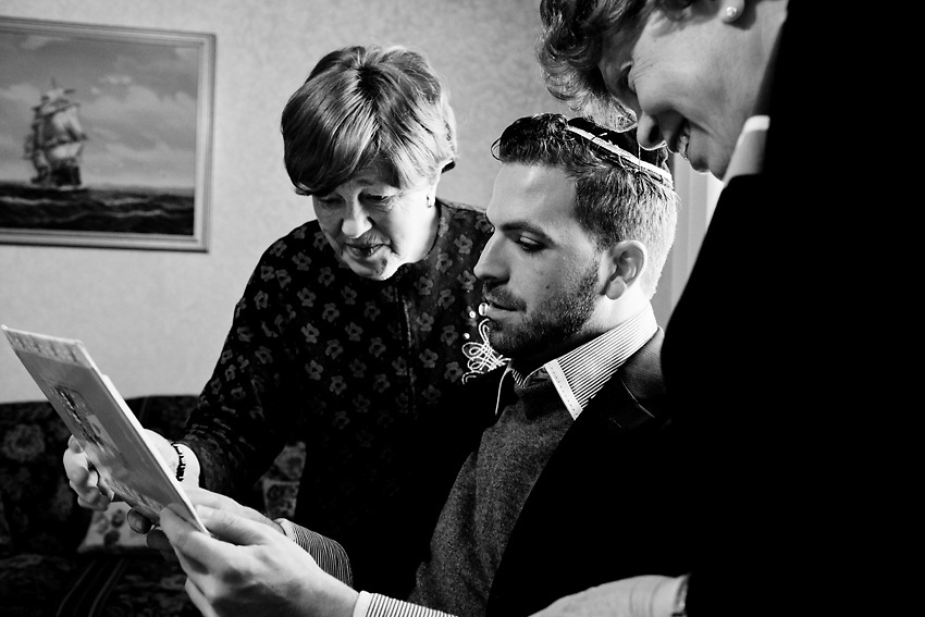 """Kal Holczler, sua nonna, Bobbi Felberbum a sinistra e sua madre, Yenti a destra, guardano un album di foto di quando Kal era piccolo. La nonna materna di Kal e` una sopravvissuta ai campi Nazisti in Ungheria. Dopo la guerra, si e` sposata ed e` venuta a vivere a Williamsburg, da dove poi, con suo marito e altri membri dell'ortodossia Ungherese, sono venuto a New Square per creare una nuova comunita`ancora piu' insulare e privata di ortodossi qui Upstate, New York. Ogni volta che la nonna rivede Kal gli chiede quando si sposera` e se tornera` a vivere vicino alla sua famiglia. Kal, tira su le spalle e risponde sempre nello stesso modo: """"Presto nonna. presto."""" Non se la sente di dire la verita', non vuole creare ulteriore tensione nella famiglia.  Foto scattata il 9 Marzo, 2014."""