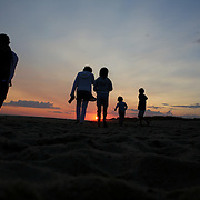 A family walk along the beach at sunset in the height of summer on Cisco Beach, Nantucket, Nantucket Island, Massachusetts, USA. Photo Tim Clayton