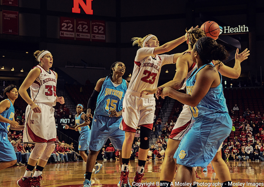 University of Nebraska's women basketball player Emily Cady reaches for rebound over Southern University players as Jordan Hooper looks on.