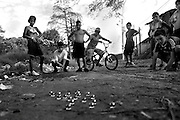 Gerardo, 14, shoots marbles with a group of friends in the streets of Los Pinos.