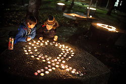 "© Licensed to London News Pictures . 01/12/2013 . Manchester , UK . Two boys kneel beside candles arranged in the shape of a ribbon , in the park . World AIDS Day commemoration in Sackville Park , Manchester , this evening (Sunday 1st December 2013) including a candle-lit procession around the city's "" Gay Village "" . Photo credit : Joel Goodman/LNP"