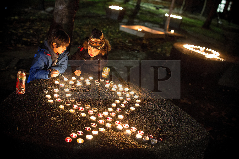 """© Licensed to London News Pictures . 01/12/2013 . Manchester , UK . Two boys kneel beside candles arranged in the shape of a ribbon , in the park . World AIDS Day commemoration in Sackville Park , Manchester , this evening (Sunday 1st December 2013) including a candle-lit procession around the city's """" Gay Village """" . Photo credit : Joel Goodman/LNP"""