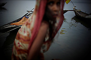 A woman on the north shore of Bhola.?This area in the south of Bangladesh has been called ground zero of climate-change due to heavy river and ocean erosion. The lowlying area is also hugely affected by cyclones and rising sea-levels...By the Mouth of Ganges, at the Bay of Bengal is the Island of Bhola. This home of about two million people is considered to be ground zero of climate change. Half the island has disappeared in the past 40 years, and according to scientists the pace is not going to slow down. People pack up and leave as the water get closer. Some to a nearby embankment, while those with enough money move further inland, but for most life move on until the inevitable. It's always about survival for the people in one of the worlds poorest countries...Photo by: Eivind H. Natvig/MOMENT
