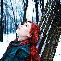 Girl with red hair gazing upward wearing a winter coat and tartan scarf leaning on a tree in a forest in with snow