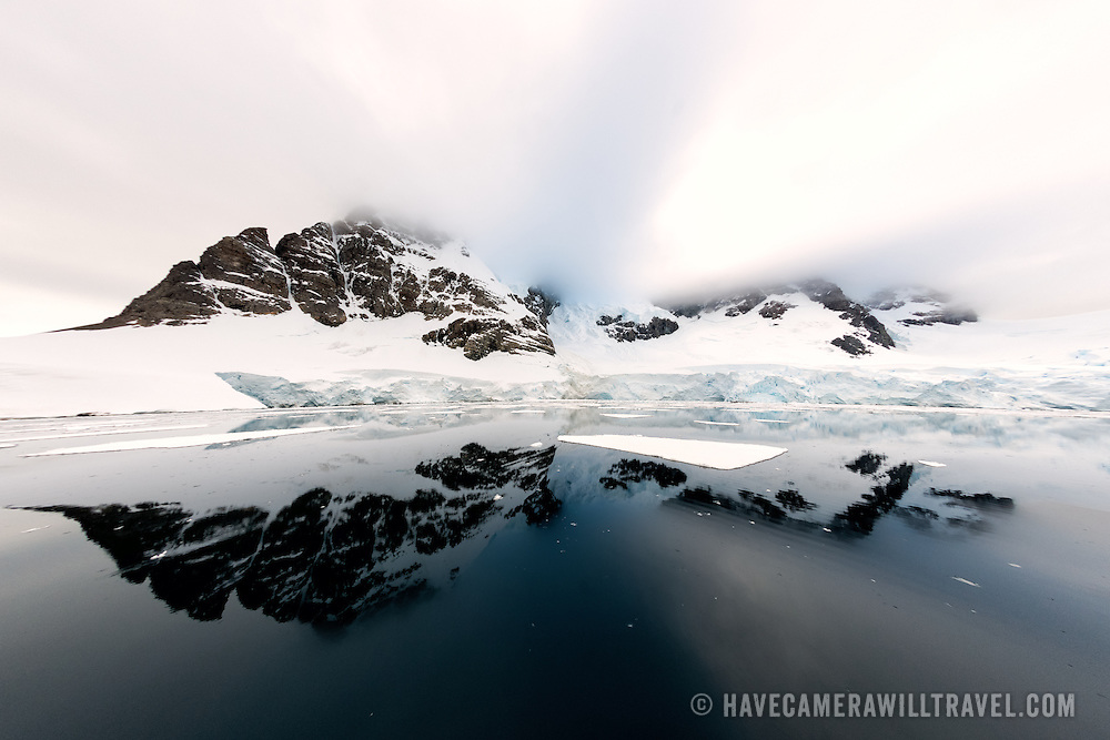 """Some of the rugged mountains rising up along the shore of the Lemaire Channel are reflected on glassy calm waters of the Lemaire Channel on the Antarctic Peninsula's western side. The Lemaire Channel is sometimes referred to as """"Kodak Gap"""" in a nod to its famously scenic views."""