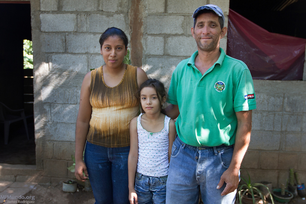 Family portrait of Santos Rene Valverde (right), 39, wife Estela Yaniet Espinoza Martinez, 25, and daughter Cherly, 6, in front of their home. Santos is officially the family's beekeeper affiliated to COOPSADES, a local co-op affiliated to UCASA (Union de Cooperativas Agropecuarias El Sauce). UCASA exports honey certified by the Fairtrade Labelling Organization (FLO). Santos explains that the extra money earned from the Fairtrade prize is allowing them to build a much better home. Las Tablas, El Sauce, León, Nicaragua. January 23, 2014.