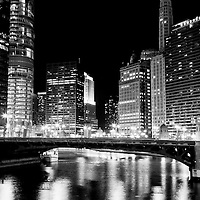 Chicago buildings at State Street Bridge (Bataan-Corregidor Memorial Bridge) at night along the Chicago River with 330 North Wabash (formerly IBM Building), Trump Tower, 333 North Michigan, London Guarantee Building / Crain Communications Building (360 North Michigan) Mather Tower (75 East Wacker Drive), Hotel 71 Building, and Seventeenth Church of Christ Scientist.
