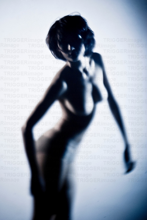 Blurred imaged of naked young woman with dark hair facing camera