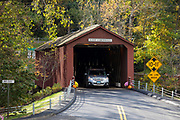Automobile drives through West Cornwall covered bridge during The Fall in Connecticut, USA