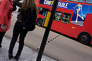 The side of a red London bus adorned with an ad for Fittflop near the awkward pigeon-toed woman standing at a crossing.