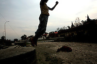 A young boy jumps off the ghats at the Pashupatinath Temple in Kathmandu on June 10, 2006. (Photo/Scott Dalton)