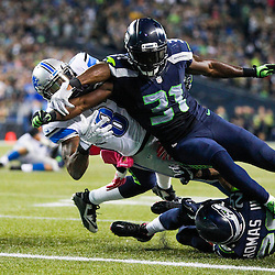 Seattle Seahawks strong safety Kam Chancellor (31) forces a fumble by Detroit Lions wide receiver Calvin Johnson (81) at the goal line during the fourth quarter of a 13-10 Seattle victory at CenturyLink Field.