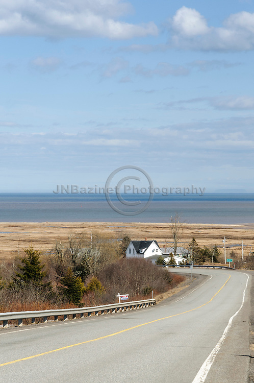 Open, curving road leading towards St. Martins New brunswick, Canada; with a house bordering the marsh off the Bay of Fundy.