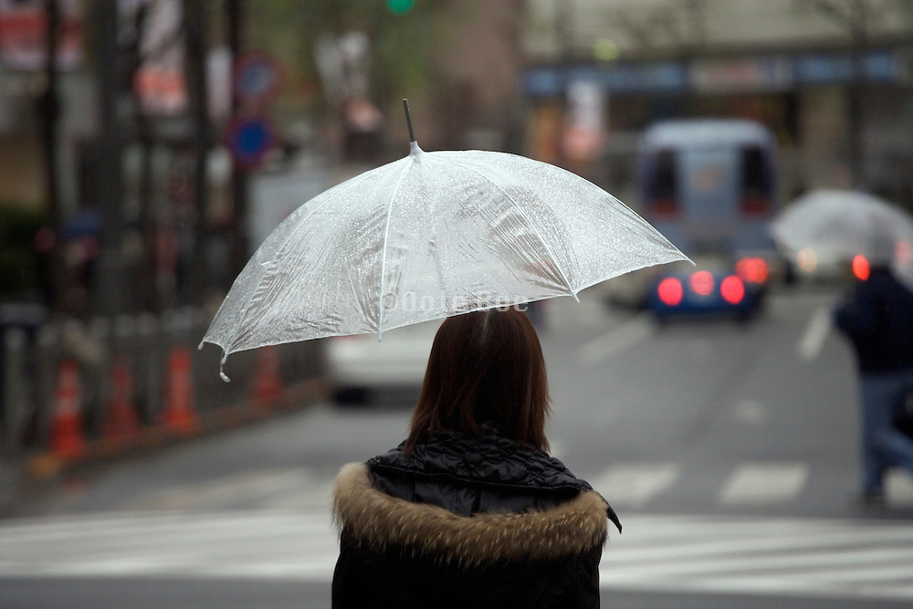 young adult woman in Tokyo with the traditional cheap transparent plastic umbrella