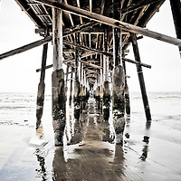 HDR photo of Newport Pier underside support posts on Balboa Peninsula in Newport Beach California. Newport Beach is a coastal community along the Pacific Ocean in Orange County California.