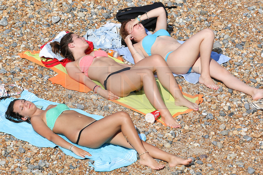 © Licensed to London News Pictures. 24/07/2014. Brighton, UK. People relaxing and sunbathing during on Brighton beach during the hottest day of the year. The weather is expected to reach temperatures around the 28C in Brighton and the South Coast. Photo credit : Hugo Michiels/LNP