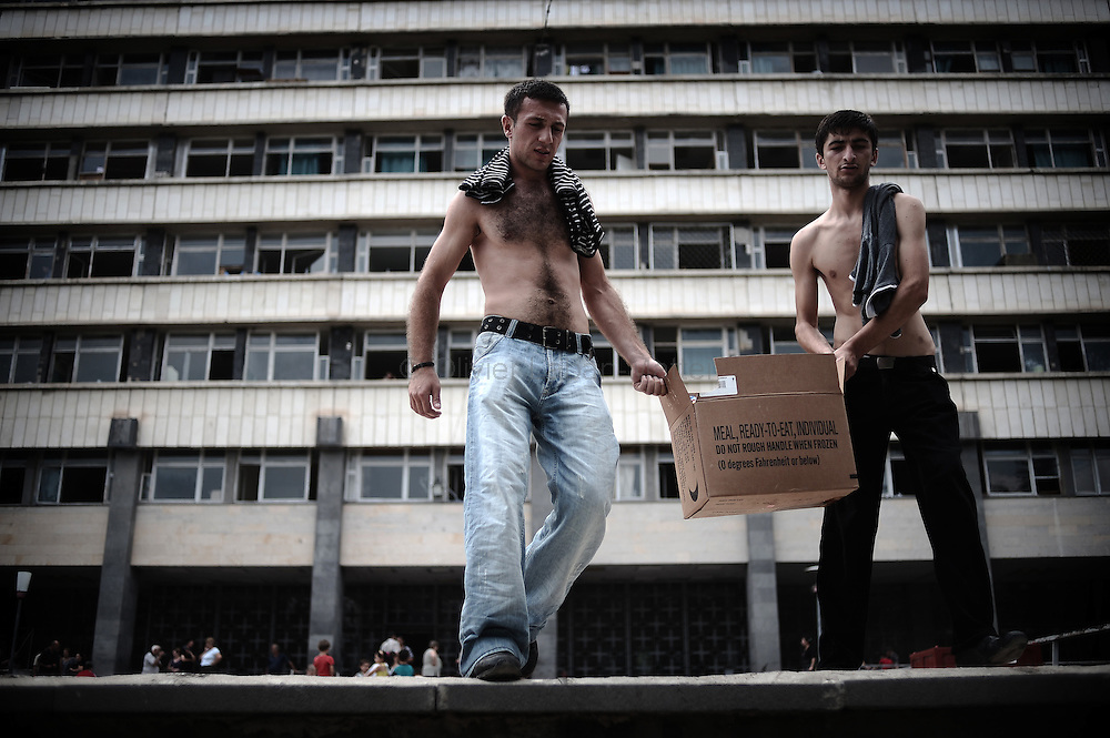 Georgian men, who fled their village after a Russian attack, carry a box of food in front of the Russian Ministry of Justice on August 29, 2008 in Tbilisi. Russia is facing an avalanche of criticism from the West over its decision to recognise the independence of two Georgian secessionist regions at the heart of the conflict: South Ossetia and Abkhazia.
