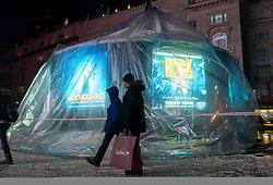 © Licensed to London News Pictures.23/12/2013. London, UK. shoppers pass the Eros statue snow globe in Piccadilly Circus London today, 23rd December 2013,  after it was damaged by high winds and heavy rain. Photo credit : Peter Kollanyi/LNP