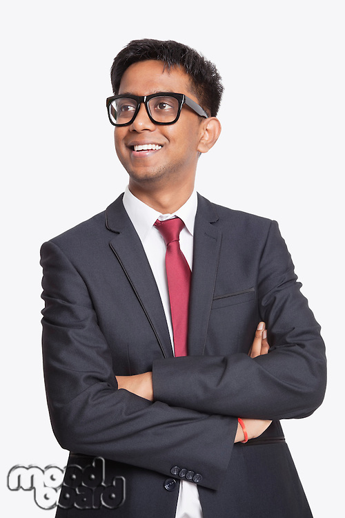 Young Asian businessman with arms crossed day dreaming against white background