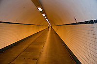 Two cyclists in a long tunnel under the river in Antwerp, Belgium.