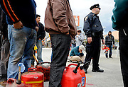 Officer Talat Awad, NYPD, strolls down the line of people waiting for gas in Park Slope, Brooklyn, including Reuben Rubin on his skateboard, Nov. 2, 2012. There was police presence at many gas stations throughout the city to keep the peace during the fuel shortage in the aftermath of Hurricane Sandy.