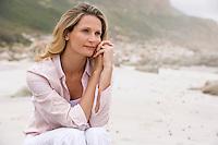 Pensive woman sitting on beach