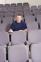 Male student sitting in lecture hall, portrait