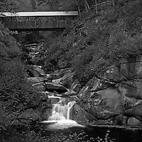 This New Hampshire B&amp;W landscape photography image of New England fall foliage peak colors at the Liberty Gorge at the Franconia Notch State Park near Lincoln, New Hampshire features the Sentinel Pine Bridge spanning across this beautiful New England gorge and a series of small waterfalls and cascades rushing into The Pool. The pool is a deep basin in the Pemigewasset River and was formed at the end of the ice age. <br />