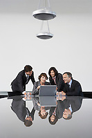 Four business colleagues using laptop at conference table
