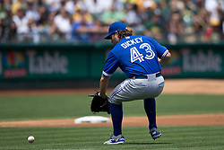 OAKLAND, CA - JULY 23:  R.A. Dickey #43 of the Toronto Blue Jays fields a ground ball hit off the bat of Brett Lawrie (not pictured) of the Oakland Athletics during the second inning at O.co Coliseum on July 23, 2015 in Oakland, California. The Toronto Blue Jays defeated the Oakland Athletics 5-2. (Photo by Jason O. Watson/Getty Images) *** Local Caption *** R.A. Dickey