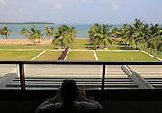 Woman relaxing on hotel balcony, Amaya Beach Resort hotel, Pasikudah bay, Eastern Province, Sri Lanka