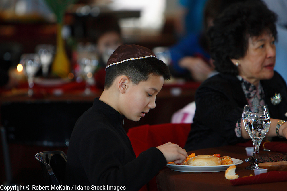 IDAHO. Boise. Asian Jewish boy dining at Bat Mitzvah. December 2008. #pa080704 MR