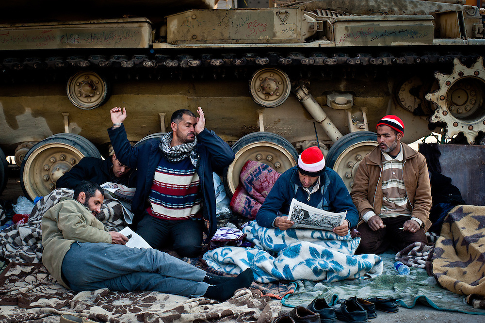 Protesters rest against the treads of an Egyptian army tank in Tahrir Square.