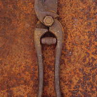 Pair of rusty old secateurs lying on rusty metal sheet