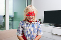 Portrait of cute girl in super hero costume at home