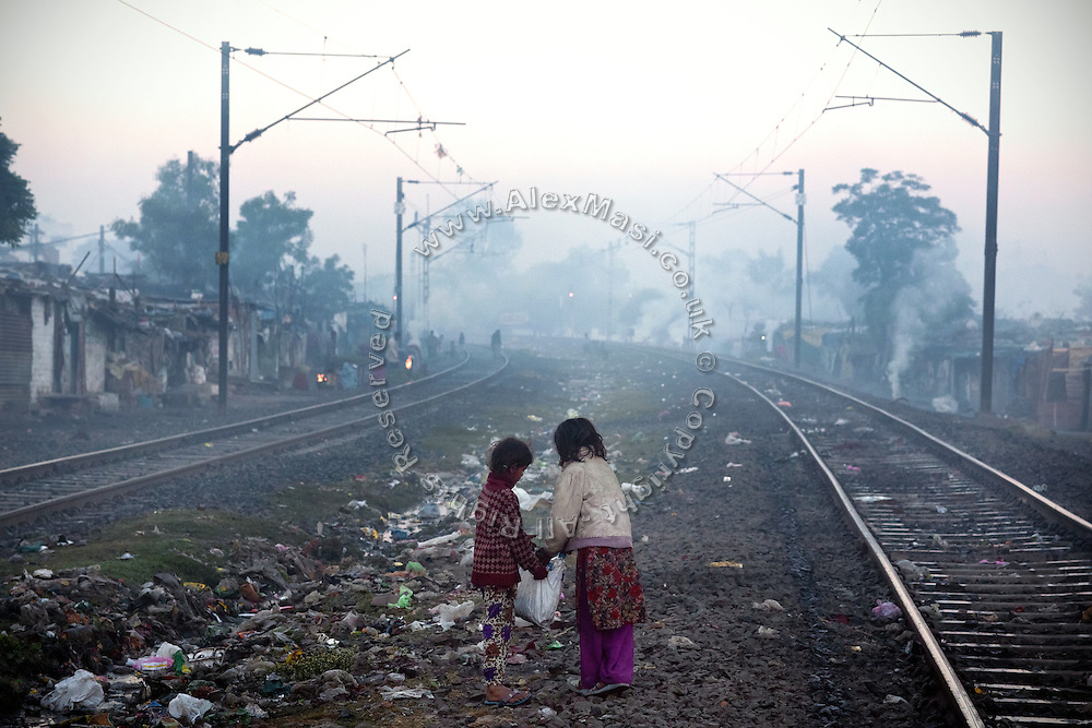 In the early morning, two siblings are collecting pieces of coal that have fallen off passing trains, along the railway tracks in New Arif Nagar, one of the water-affected colonies standing next to the abandoned Union Carbide (now DOW Chemical) industrial complex, site of the infamous 1984 gas tragedy in Bhopal, Madhya Pradesh, central India. The poisonous cloud that enveloped Bhopal left everlasting consequences that today continue to consume people's lives.